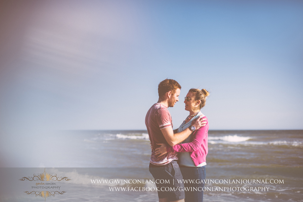 creative portrait ofVictoria and James looking at each other on the beach near  Boscombe Pier . Engagement Session in Bournemouth, Dorset by gavin conlan photography Ltd