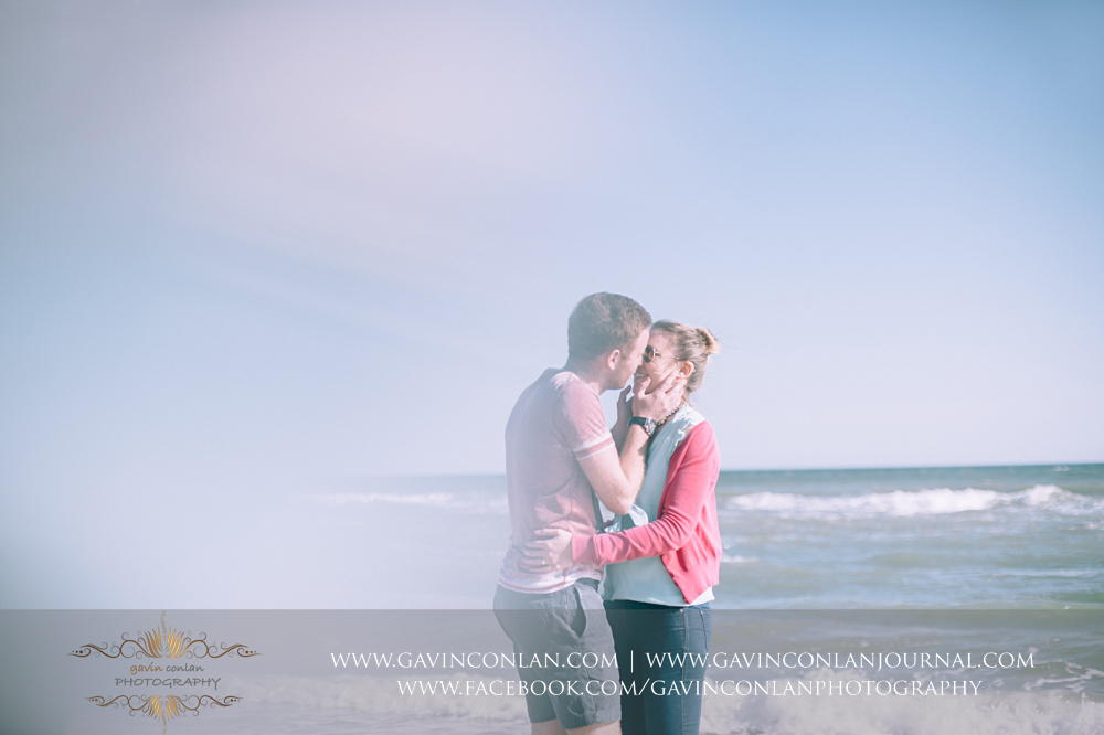 Victoria and James sharing a kiss on the beach near  Boscombe Pier .Engagement Session in Bournemouth, Dorset by gavin conlan photography Ltd