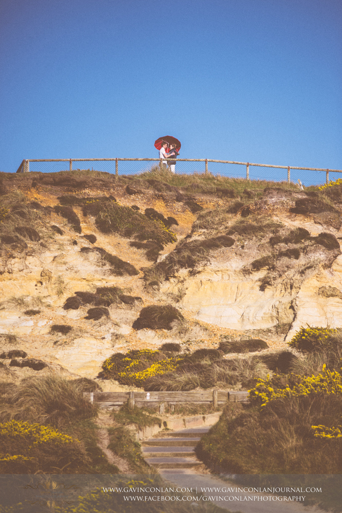 creative fine art portrait of Victoria and James looking at each other under a red heart shaped umbrella at the top of  Hengistbury Head .Engagement Session in Bournemouth, Dorset by gavin conlan photography Ltd
