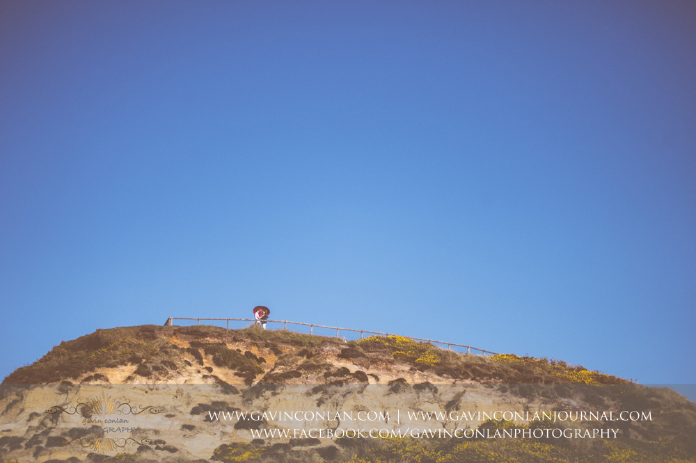 creative fine art portrait of Victoria and James underneath a red heart shaped umbrella at Hengistbury Head .Engagement Session in Bournemouth, Dorset by gavin conlan photography Ltd