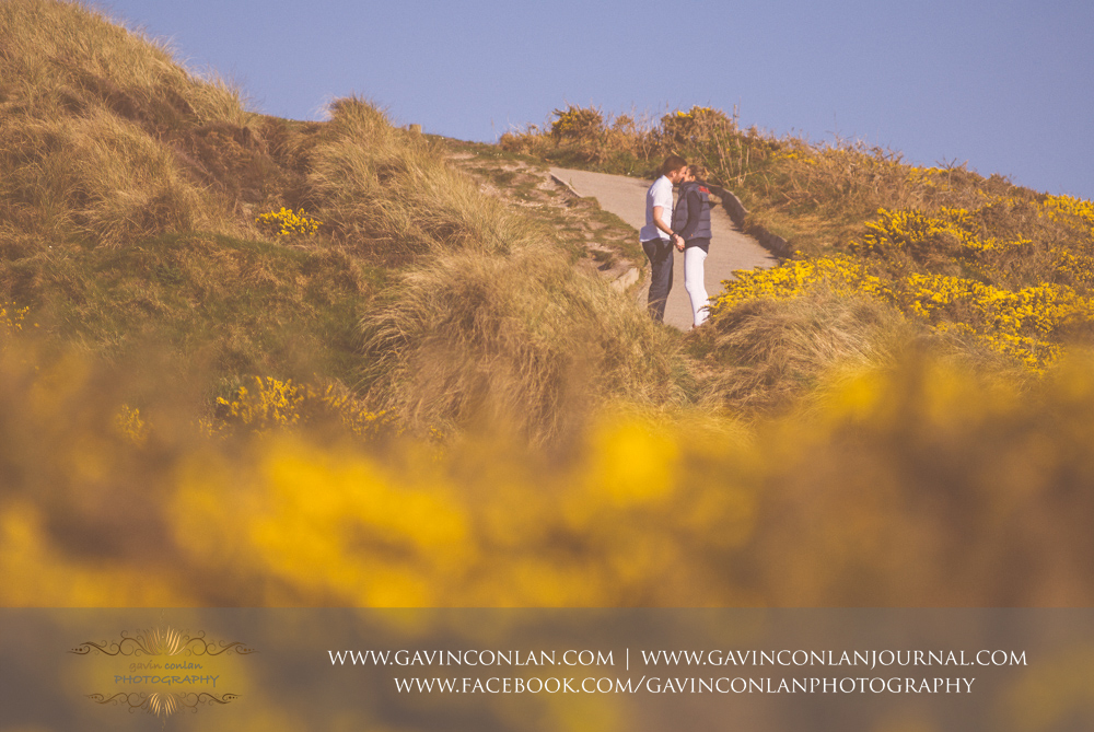 creative fine art portrait of Victoria and James sharing a kiss on the walk up to  Hengistbury Head .Engagement Session in Bournemouth, Dorset by gavin conlan photography Ltd