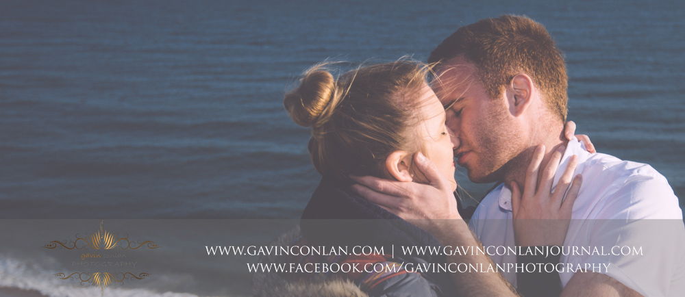 portrait of Victoria and James about to kiss at  Hengistbury Head . Engagement Session in Bournemouth, Dorset by  gavin conlan photography Ltd