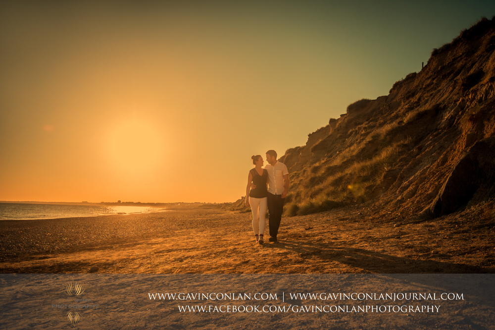 creative portrait of Victoria and James walking along the beach at Hengistbury Head at sunset.Engagement Session in Bournemouth, Dorset by gavin conlan photography Ltd