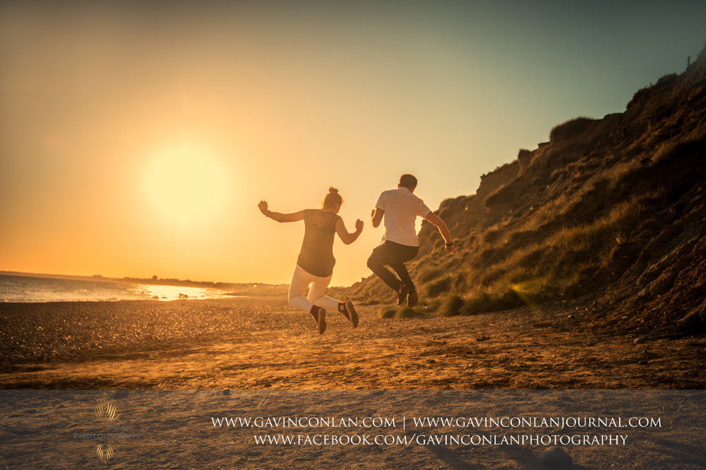 fun portrait of Victoria and James jumping in the air on the beach of  Hengistbury Head at sunset.Engagement Session in Bournemouth, Dorset by gavin conlan photography Ltd