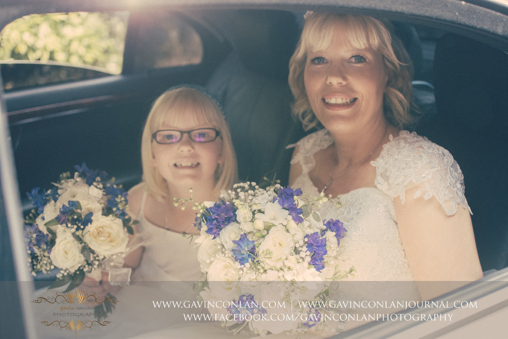 beautiful portrait of the gorgeous bride and her lovely daughter posing in the back of the wedding car.Wedding photography at The Barn Brasserie by Essex wedding photographer gavin conlan photography Ltd