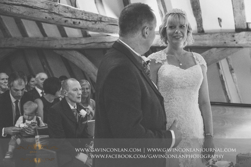 beautiful black and white ceremony photograph of the bride looking at her groom.Wedding photography at The Barn Brasserie by Essex wedding photographer gavin conlan photography Ltd