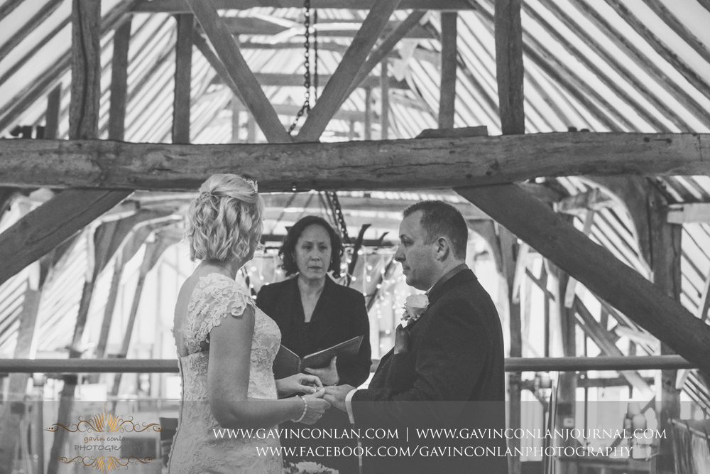 creative black and white ceremony photograph showing the brideputting the wedding ring on hergrooms finger during the service.Wedding photography at The Barn Brasserie by Essex wedding photographer gavin conlan photography Ltd