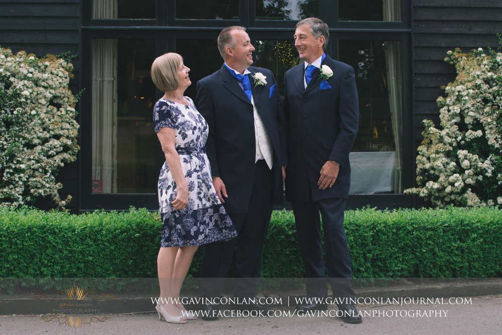 fun portrait of the groom with his parents outside The Barn.Wedding photography at The Barn Brasserie by Essex wedding photographer gavin conlan photography Ltd