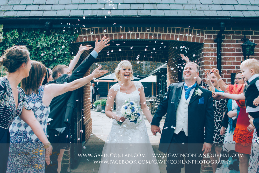 guests throwing confetti over the bride and groom.Wedding photography at The Barn Brasserie by Essex wedding photographer gavin conlan photography Ltd