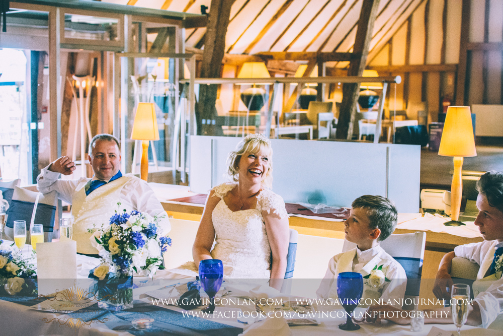 bride and groom laughing during the speeches. Wedding photography at The Barn Brasserie by Essex wedding photographer gavin conlan photography Ltd