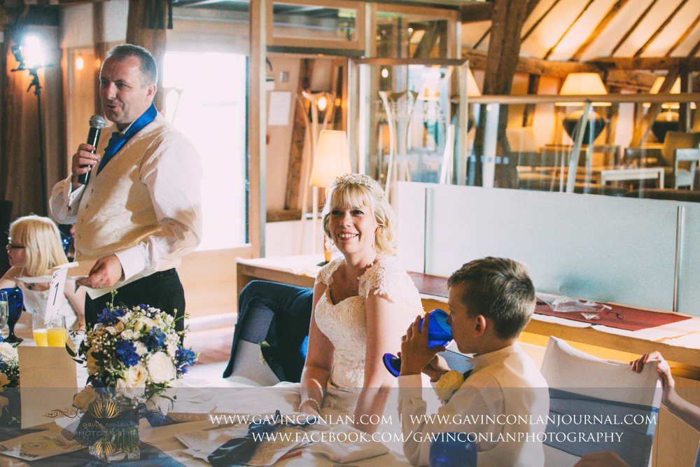 the groom during his speech with his bride looking on smiling.Wedding photography at The Barn Brasserie by Essex wedding photographer gavin conlan photography Ltd