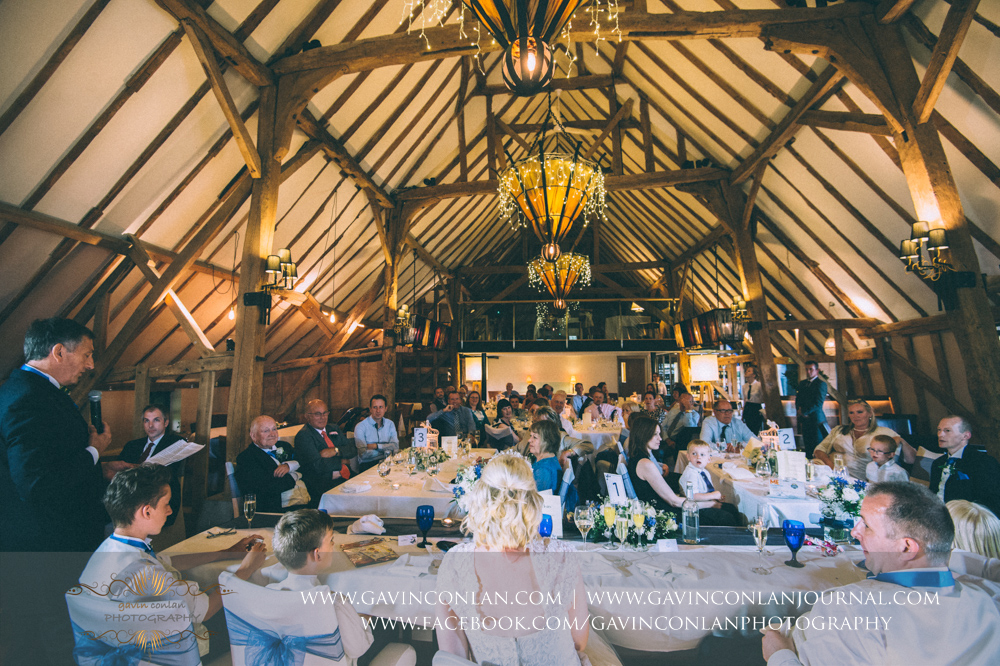 the father of the groom during his speech with all the guests in the background.Wedding photography at The Barn Brasserie by Essex wedding photographer gavin conlan photography Ltd