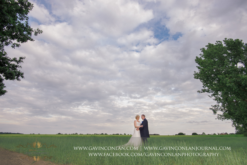 creative portrait of the bride and groom in the field opposite The Barn.Wedding photography at The Barn Brasserie by Essex wedding photographer gavin conlan photography Ltd