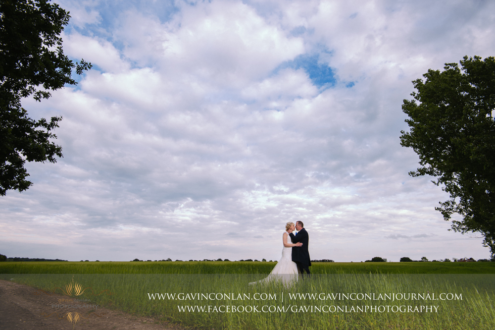 creative portrait of the bride and groom about to kiss in the field opposite The Barn.Wedding photography at The Barn Brasserie by Essex wedding photographer gavin conlan photography Ltd