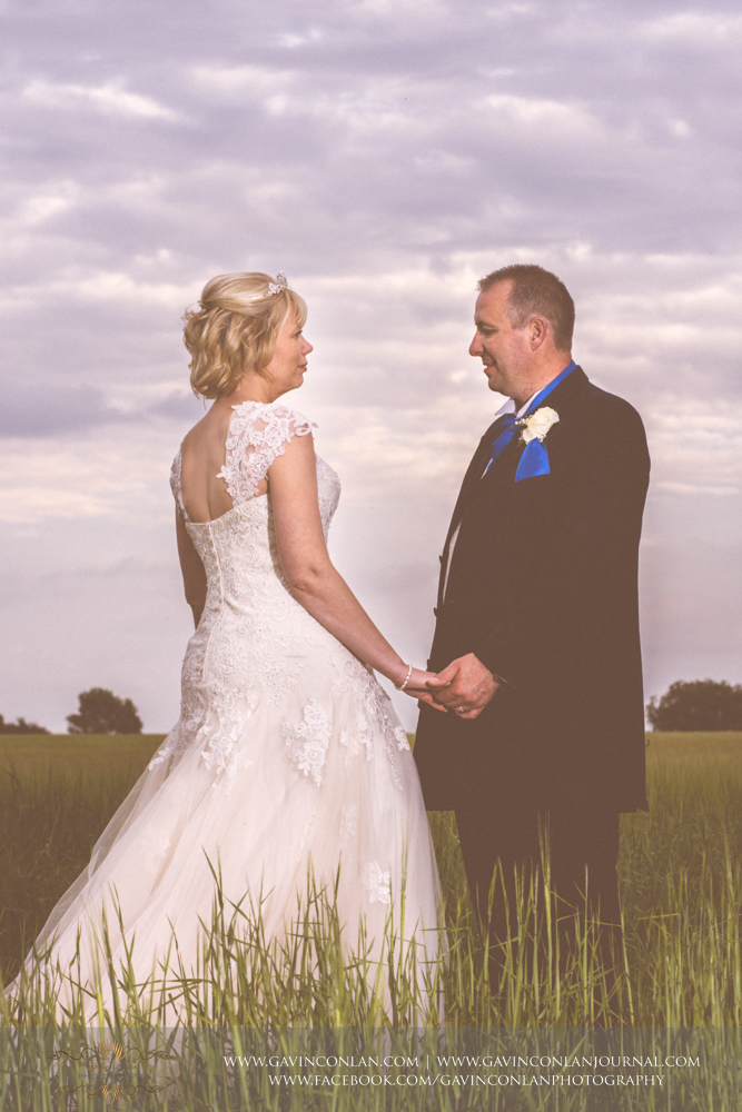absolutely stunning fashion portrait of the bride and groom in the field opposite The Barn.Wedding photography at The Barn Brasserie by Essex wedding photographer gavin conlan photography Ltd
