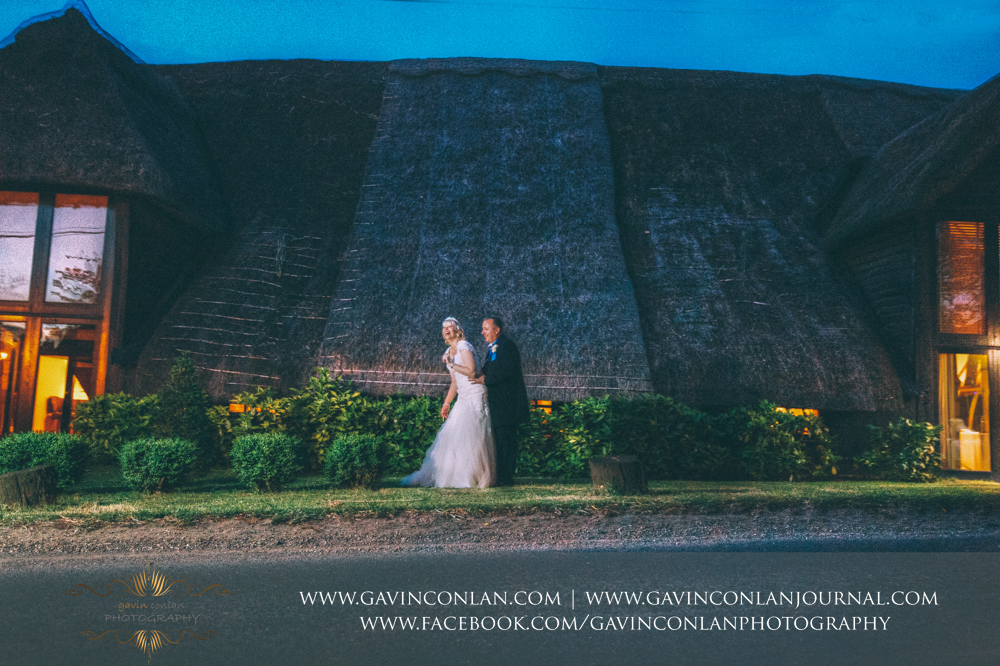 creative night time portrait of the bride and groom outside The Barn having fun together. Wedding photography at The Barn Brasserie by Essex wedding photographer gavin conlan photography Ltd