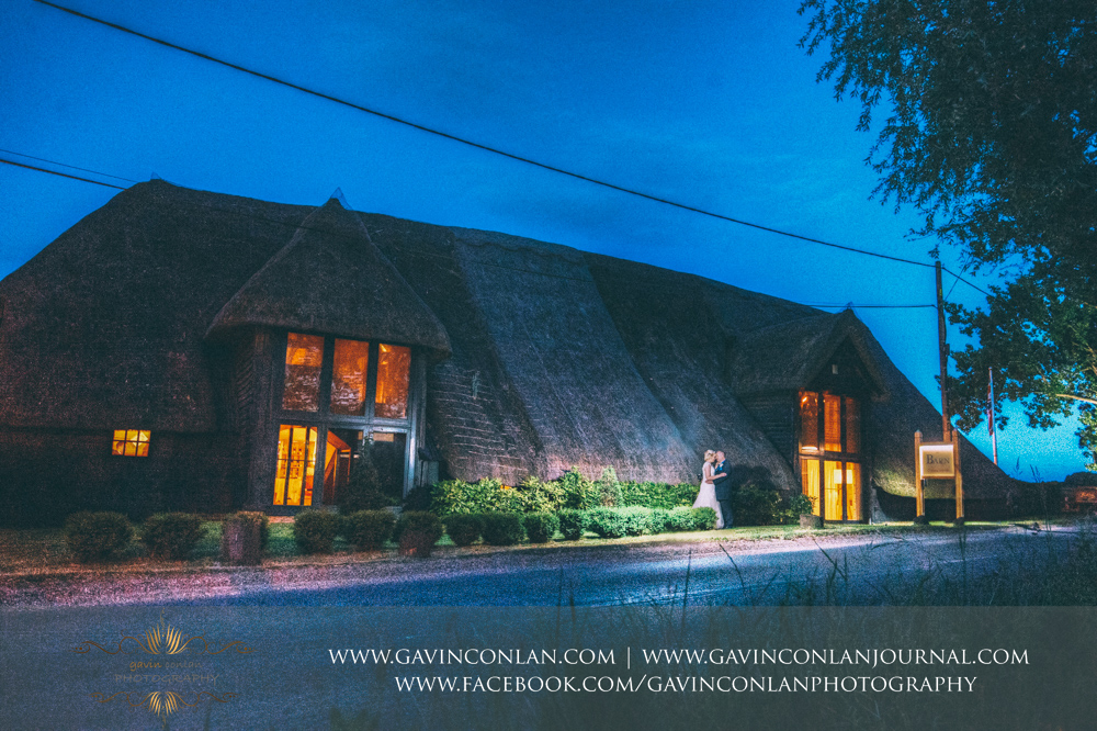 stunning night time portrait of the bride and groom with the whole of The Barn in the background.Wedding photography at The Barn Brasserie by Essex wedding photographer gavin conlan photography Ltd