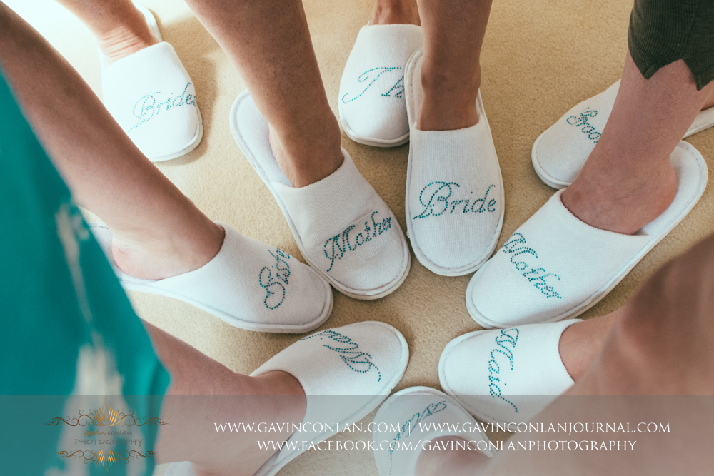 fun portrait showcasing the girls wearing their bridal party slippers.Wedding photography at Gosfield Hall by Essex wedding photographer gavin conlan photography Ltd