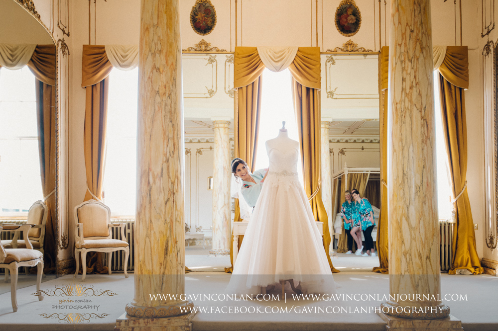 fun portrait of the bride peering round her wedding dress with her bridesmaids in the reflection of the mirrorin The Rococco Suite.Wedding photography at Gosfield Hall by Essex wedding photographer gavin conlan photography Ltd
