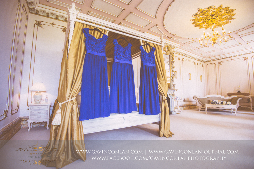 creative detail photograph showcasing the three bridesmaids dresses hanging on the four poster bed in The Rococco Suite.Wedding photography at Gosfield Hall by Essex wedding photographer gavin conlan photography Ltd