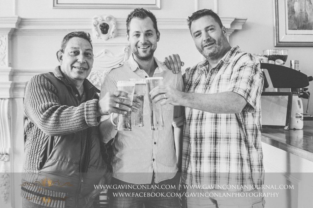 fun portrait of the groom with his best man and Harvey celebrating with 3 pints of carlsberg in the Bar and Disco room.Wedding photography at Gosfield Hall by Essex wedding photographer gavin conlan photography Ltd