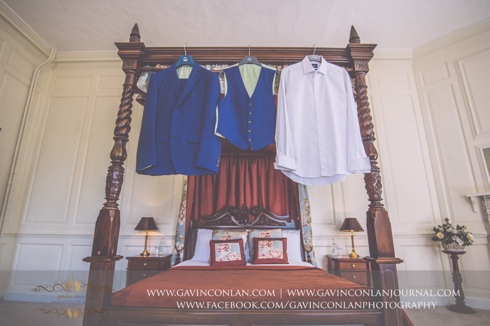 creative detail photograph of the grooms suit hanging on the four poster bed in The Kings Apartment.Wedding photography at Gosfield Hall by Essex wedding photographer gavin conlan photography Ltd