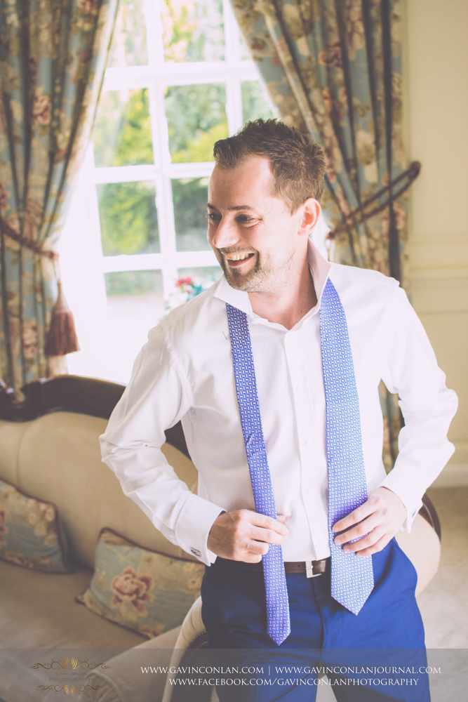 portrait of the groom smiling whilst holding his tie in The Kings Apartment. Wedding photography at Gosfield Hall by Essex wedding photographer gavin conlan photography Ltd