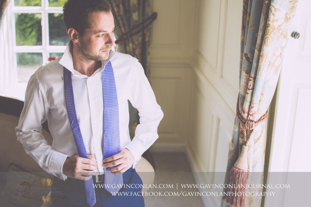 fashion portrait of the groom getting ready in The Kings Apartment. Wedding photography at Gosfield Hall by Essex wedding photographer gavin conlan photography Ltd