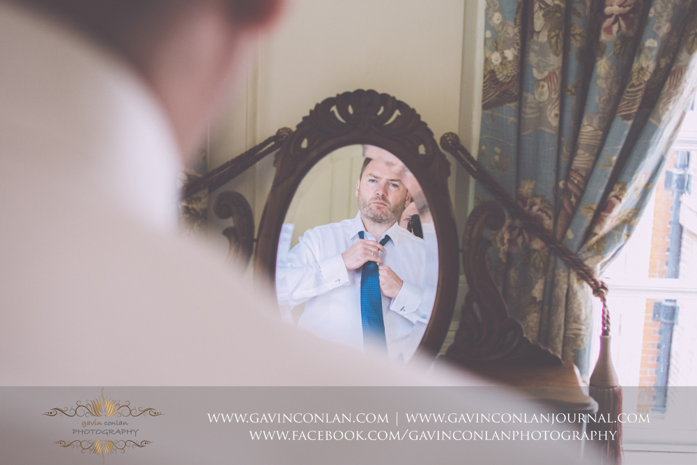 creative portrait of the best man getting dressed in The Kings Apartment.Wedding photography at Gosfield Hall by Essex wedding photographer gavin conlan photography Ltd