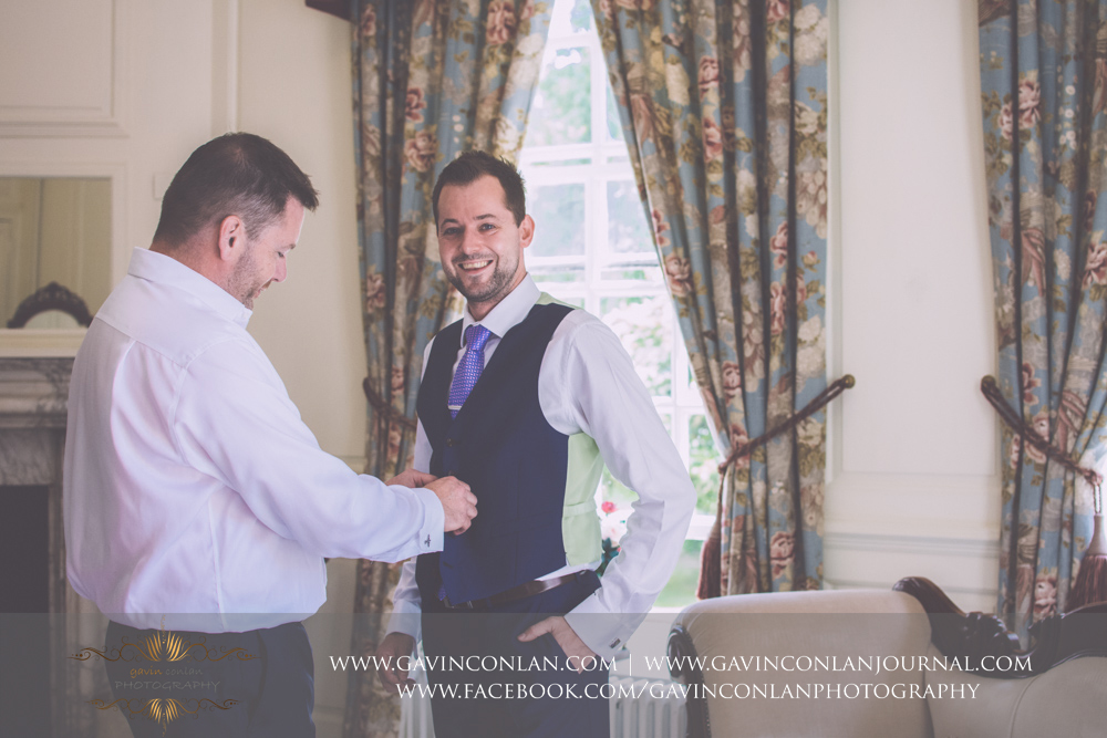 portrait of the best man helping the groom get dressed in The Kings Apartment.Wedding photography at Gosfield Hall by Essex wedding photographer gavin conlan photography Ltd