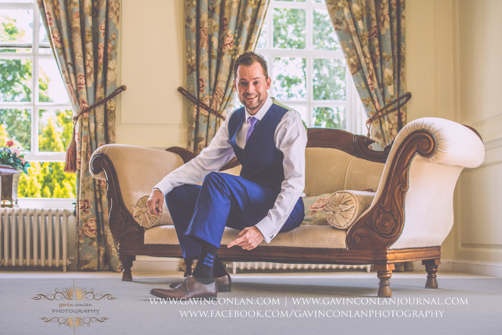 creative and fun portrait of the groom pointing to the socks his bride bought him in The Kings Apartment. Wedding photography at Gosfield Hall by Essex wedding photographer gavin conlan photography Ltd