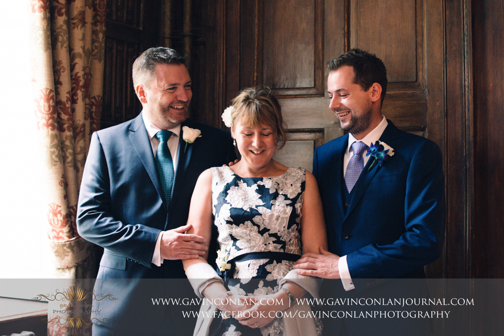 fun portrait of the groom, his mother and his best man/step dad in The Prophets Chamber.Wedding photography at Gosfield Hall by Essex wedding photographer gavin conlan photography Ltd