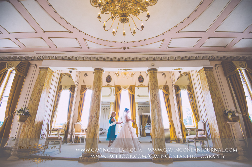 creative portrait of the brides mother helping the bride get dressed in The Rococco Suite. Wedding photography at Gosfield Hall by Essex wedding photographer gavin conlan photography Ltd