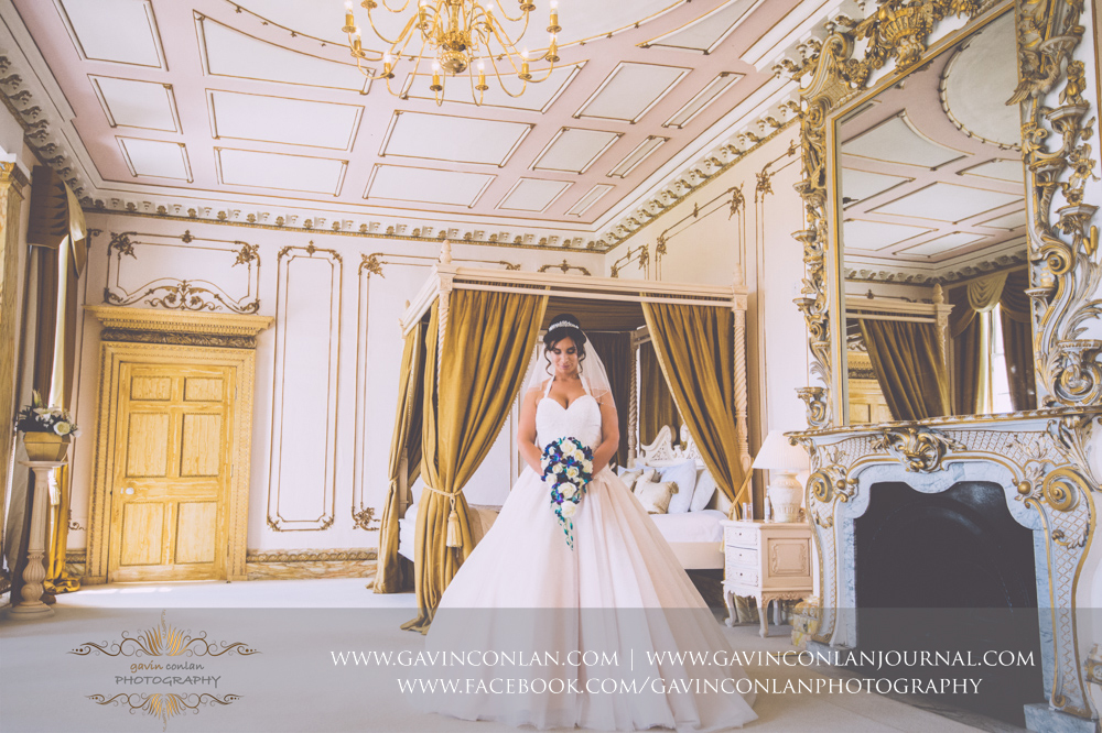 gorgeous portrait of the bride looking down at her wedding bouquet in The Rococco Suite.Wedding photography at Gosfield Hall by Essex wedding photographer gavin conlan photography Ltd