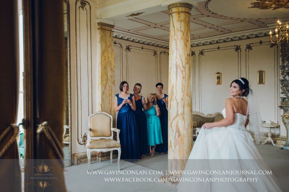 creative and fun bridal portrait with her bridesmaids and her mother looking on in the background, The Rococco Suite.Wedding photography at Gosfield Hall by Essex wedding photographer gavin conlan photography Ltd