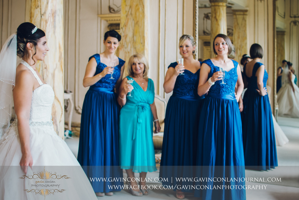 creative portrait of the bridesmaids and the brides mother looking at the bride in The Rococco Suite.Wedding photography at Gosfield Hall by Essex wedding photographer gavin conlan photography Ltd