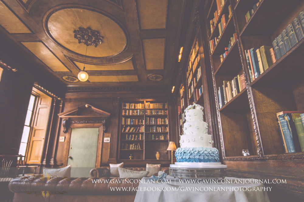creative detail photograph of the wedding cake on display in the library.Wedding photography at Gosfield Hall by Essex wedding photographer gavin conlan photography Ltd