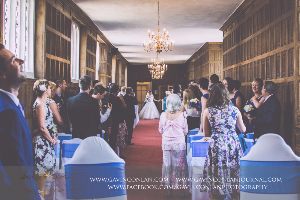 beautiful expression of the groom as his bride begins her walk down the aisle in The Queens Gallery. Wedding photography at Gosfield Hall by Essex wedding photographer gavin conlan photography Ltd