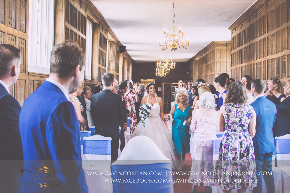 portrait of the bride and her mother walking down the aisle in The Queens Gallery.Wedding photography at Gosfield Hall by Essex wedding photographer gavin conlan photography Ltd