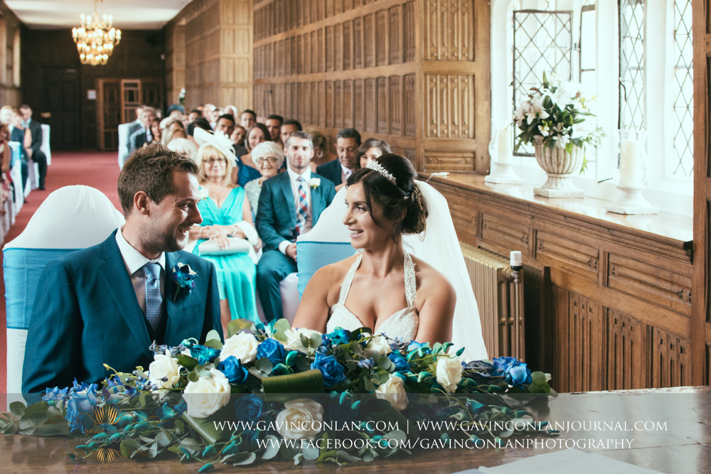 creative wedding ceremony photograph of the bride and groom sitting down looking at each other smiling in The Queens Gallery.Wedding photography at Gosfield Hall by Essex wedding photographer gavin conlan photography Ltd