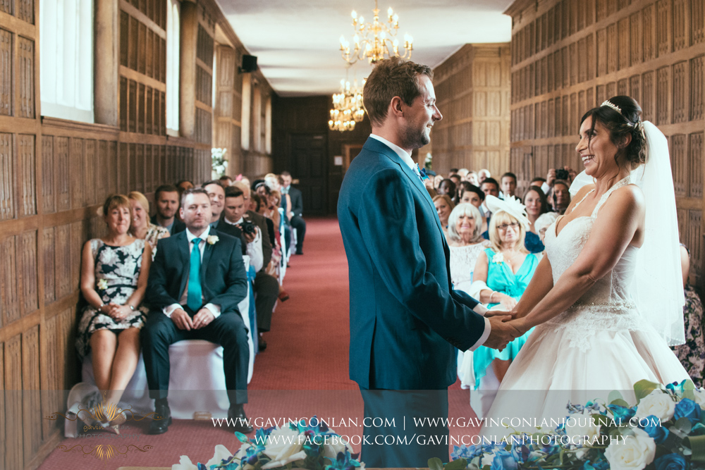 creative wedding ceremony photograph of the bride and groom holding hands andlooking at each other smiling in The Queens Gallery.Wedding photography at Gosfield Hall by Essex wedding photographer gavin conlan photography Ltd