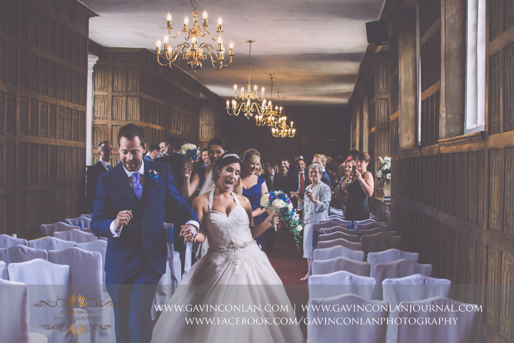 brilliant portrait of the bride and groom dancing down the aisle with their guests in the background smiling in The Queens Gallery.Wedding photography at Gosfield Hall by Essex wedding photographer gavin conlan photography Ltd