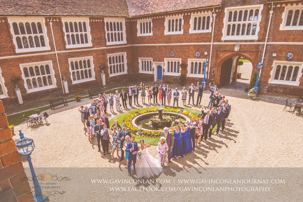 creative group photograph of the bride and groom with all their guests standing around the fountain in a heart shaped in the inner courtyard of Gosfield Hall.Wedding photography at Gosfield Hall by Essex wedding photographer gavin conlan photography Ltd
