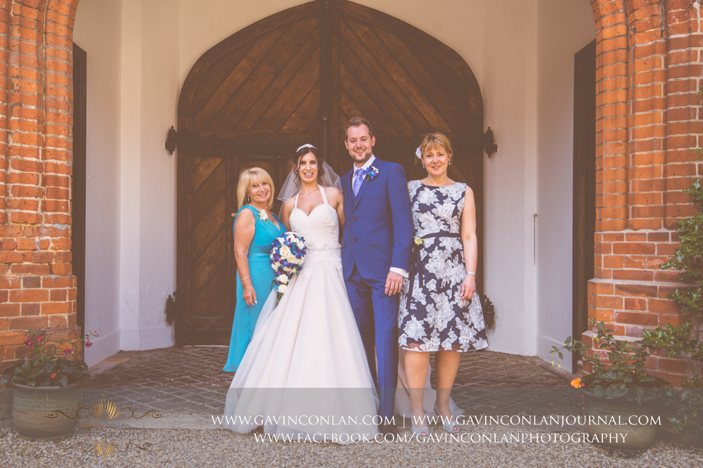 portrait of the bride and groom with the brides mother and the grooms mother in the inner courtyard of Gosfield Hall.Wedding photography at Gosfield Hall by Essex wedding photographer gavin conlan photography Ltd