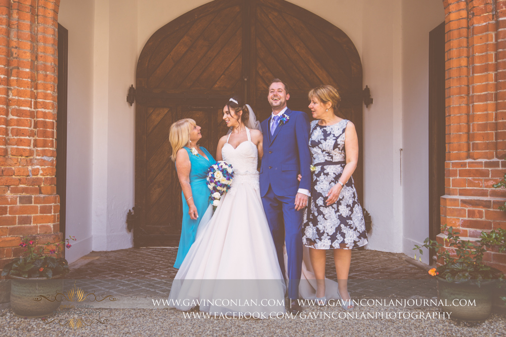 creative portrait of the bride and groom with the brides mother and the grooms mother in the inner courtyard of Gosfield Hall.Wedding photography at Gosfield Hall by Essex wedding photographer gavin conlan photography Ltd