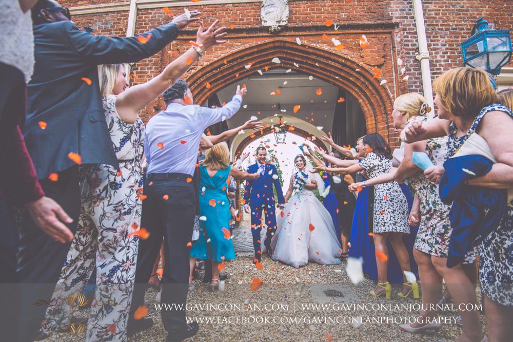 the classic confetti photograph taken in the inner courtyard of Gosfield Hall.Wedding photography at Gosfield Hall by Essex wedding photographer gavin conlan photography Ltd