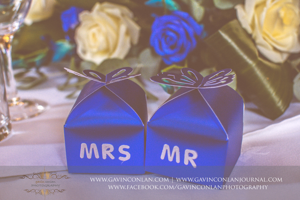 creative detail photograph of the blue Mr and Mrs boxes on the top table in the ballroom.Wedding photography at Gosfield Hall by Essex wedding photographer gavin conlan photography Ltd