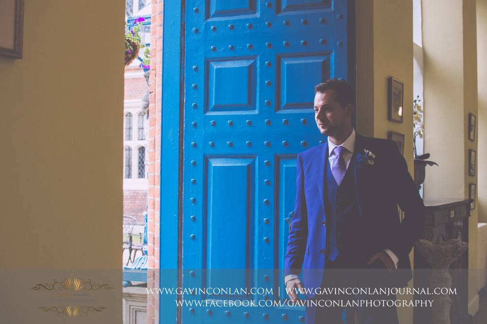 classic and fine art portrait of the groom looking out into the inner courtyard of Gosfield Hall.Wedding photography at Gosfield Hall by Essex wedding photographer gavin conlan photography Ltd