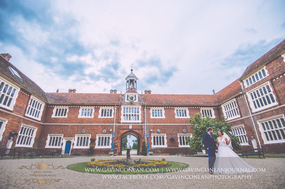 creative portrait of the bride and groom in the inner courtyard of Gosfield Hall.Wedding photography at Gosfield Hall by Essex wedding photographer gavin conlan photography Ltd