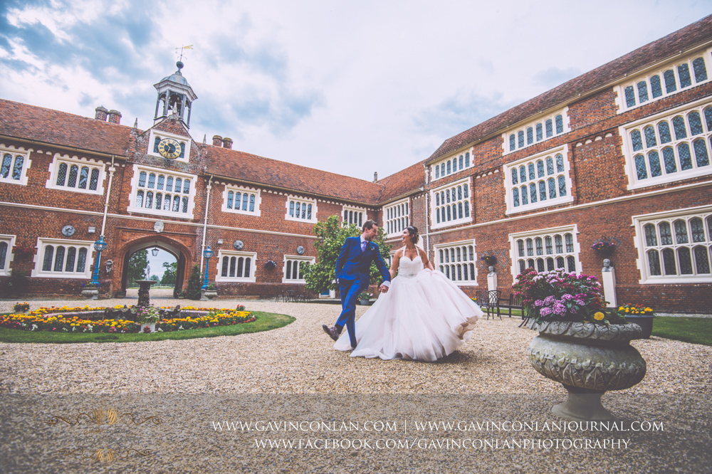 creative and fun portrait of the bride and groom in the inner courtyard of Gosfield Hall.Wedding photography at Gosfield Hall by Essex wedding photographer gavin conlan photography Ltd